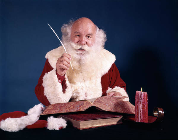 Jolly Holiday Photograph - 1960s Santa Sitting At Desk Looking by Vintage Images