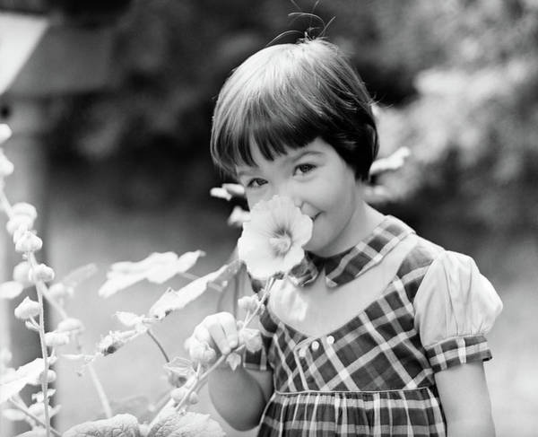 Hollyhock Photograph - 1960s Smiling Little Girl Smelling by Vintage Images