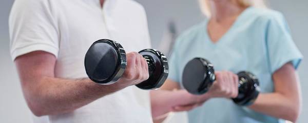 Wall Art - Photograph - Nurse Showing Man How To Use Hand Weights by Science Photo Library