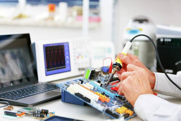 Technological Wall Art - Photograph - Person Repairing Electronic Circuit Board by Wladimir Bulgar