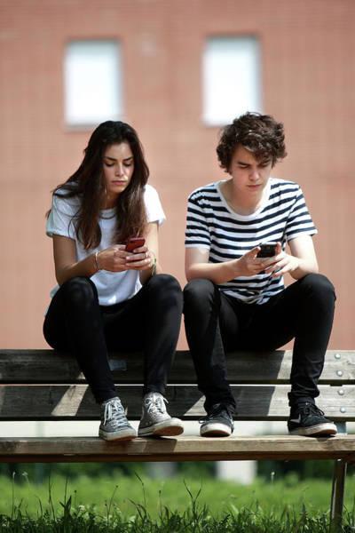 Smartphone Photograph - Teenage Couple Using Smart Phones by Mauro Fermariello