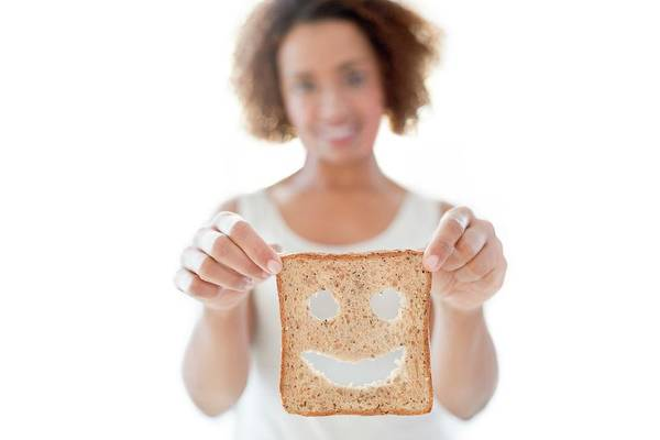 Wall Art - Photograph - Woman Holding Bread With Smiley Face by Science Photo Library