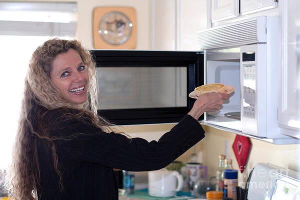 Photograph - Woman Puts Food In Oven by Gunter Nezhoda
