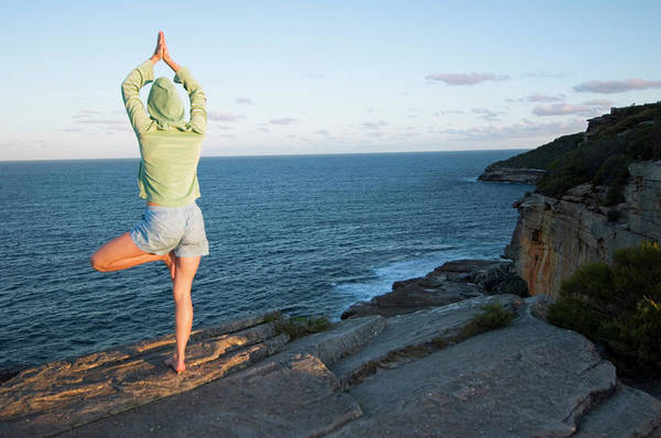 Ocean Breeze Photograph - Yoga On Rocky Outcrop Above Ocean by Lars Schneider