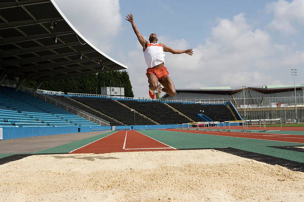 Runway Photograph - Athlete Performing A Long Jump by Gustoimages/science Photo Library