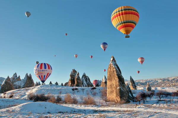 Nevsehir Photograph - Hot Air Balloons Over Snow Covered Rock by Izzet Keribar
