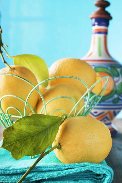 Wall Art - Photograph - Fresh Lemons With Leaves In Wire Basket by Foodcollection