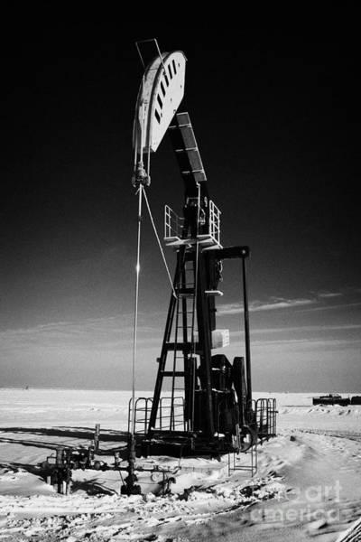 Pump Jack Wall Art - Photograph - oil pumpjack in winter snow Forget Saskatchewan Canada by Joe Fox