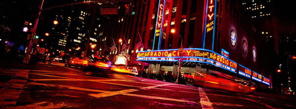 Radio City Music Hall Photograph - Low Angle View Of Buildings Lit by Panoramic Images