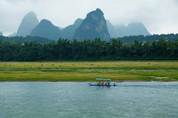 Raft Photograph - A Bamboo Raft Along The Li River In by Nisa And Ulli Maier Photography