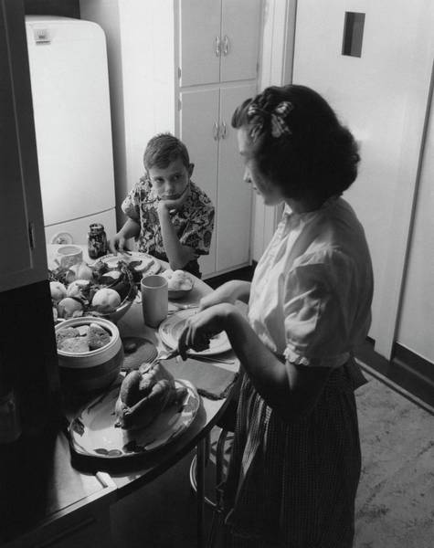 Dinner Plate Photograph - A Boy Watching His Mother Prepare Dinner by Luis Lemus