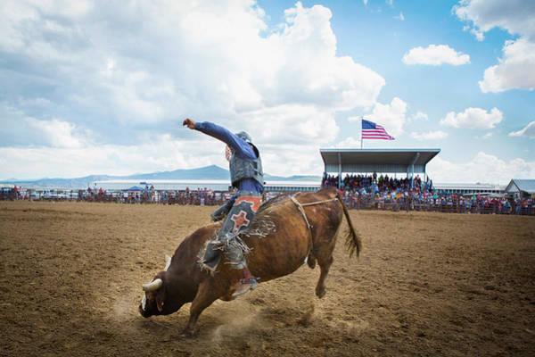 Sitting Bull Photograph - A Bull Rider Hold On To A Bucking Bull by Nicholas J Reid