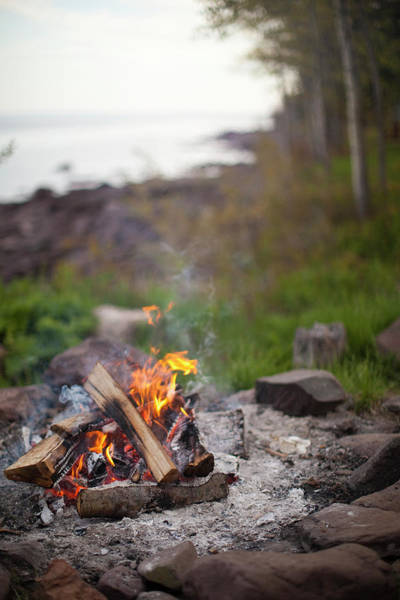 Wall Art - Photograph - A Camp Fire Burns At Sunset With A Lake by David Ellis