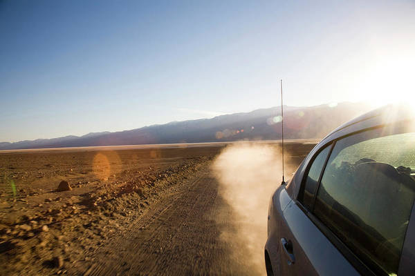Brighter Side Photograph - A Car Speeds Down A Sandy Road Leaving by Michael Hanson