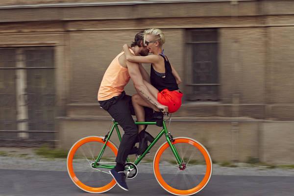 A Couple Biking Through The City Art Print by Justin Case