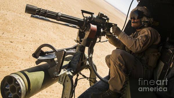 Firepower Photograph - A Crew Chief Mounts A M134 Minigun by Stocktrek Images