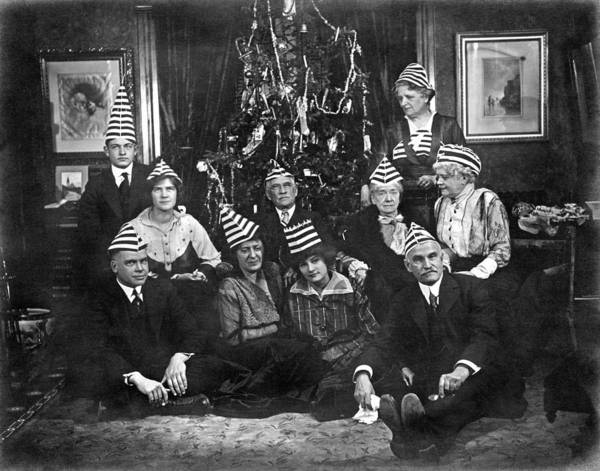 Nightime Photograph - A Family With An Interesting Christmas Tradition Of Strange Hats by Underwood Archives