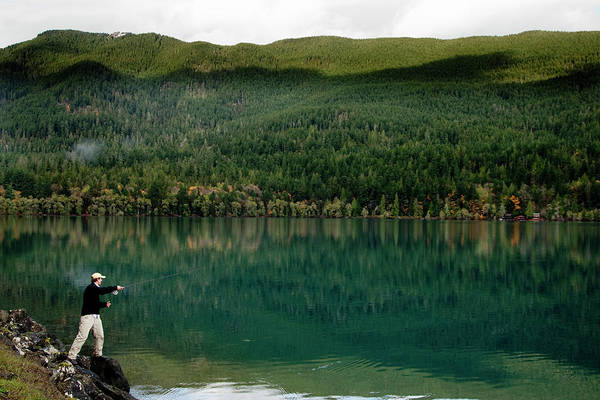 Wall Art - Photograph - A Fly Fisherman Cast His Line Into Lake by Jordan Siemens