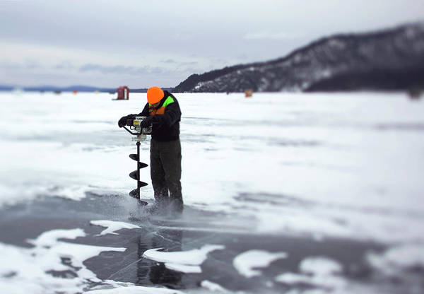 Wall Art - Photograph - A Ice Fisherman Uses An Auger To Drill by David McLain