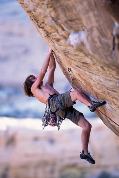 Hanging Rock Photograph - A Male Rock Climber Climbing by Corey Rich