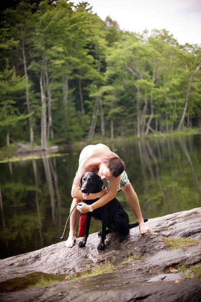 Fetch Photograph - A Man And His Dog Play Next To A Lake by Christopher Cumming