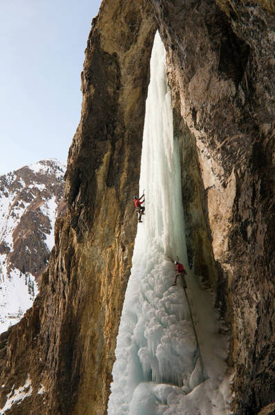 Hanging Rock Photograph - A Man And Woman Ice Climbing A Frozen by Kennan Harvey