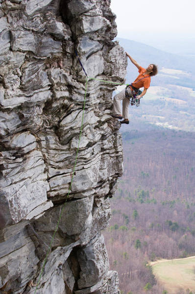 Scaling Photograph - A Man Climbs A Rock Face by Andrew Kornylak