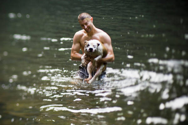 Backwoods Wall Art - Photograph - A Man Holds A Wet Bulldog by Andrew Kornylak