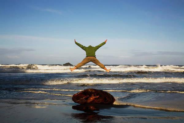 Exuberance Photograph - A Man Jumps Enthusiastically Off A Log by Michael Hanson