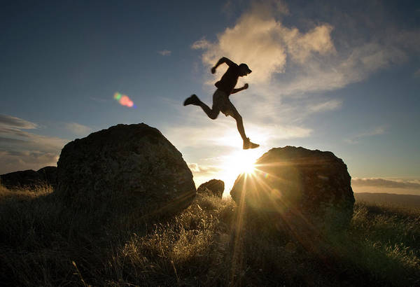 Exuberance Photograph - A Man Leaps Between Two Boulders by Eric Rorer