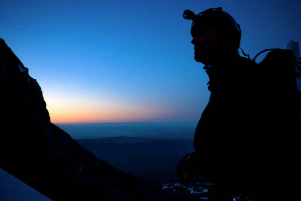 Wall Art - Photograph - A Man Looks Up At The Summit Of Mount by Kirk Mastin