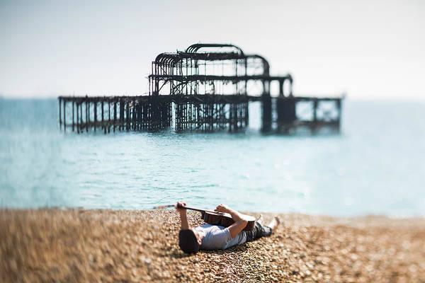 Palace Pier Wall Art - Photograph - A Man Lying On A Beach With A Guitar by Richard Boll