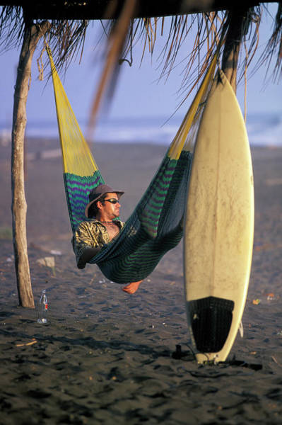 Pasquale Photograph - A Man Relaxes In A Hammock On The Beach by Corey Rich