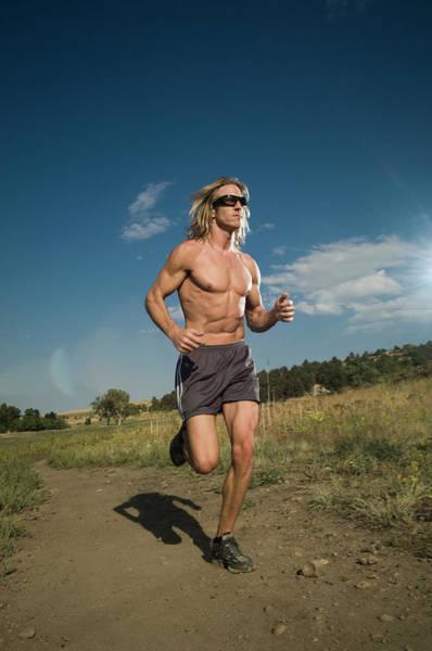 Physique Photograph - A Man Runs On A Trail Near Boulder by Andrew Kornylak