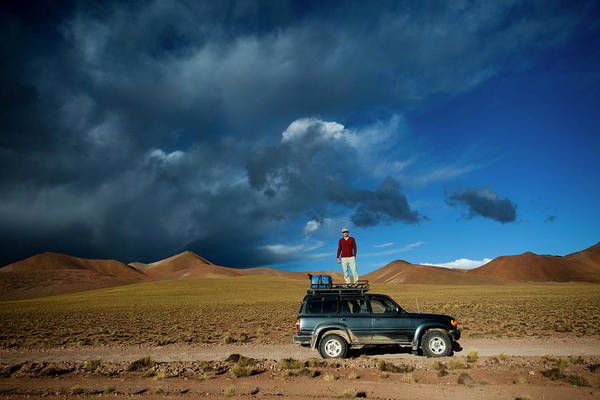 Wall Art - Photograph - A Man Stands On The Roof Of His Truck by Michael Hanson