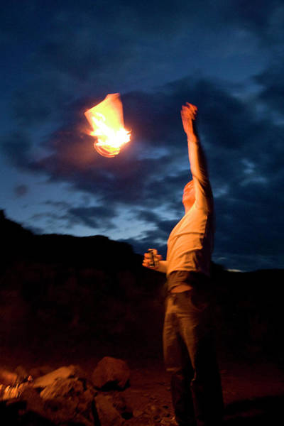 Kittitas County Wall Art - Photograph - A Man Tossing A Piece Of Burning Paper by Jordan SIemens