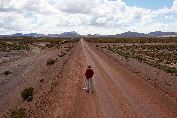 Salar De Atacama Photograph - A Man Urinates On A Lonely Dirt Road by Michael Hanson