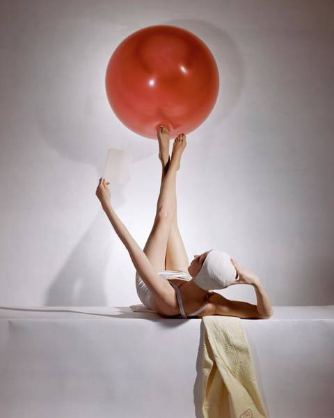 Yellow Background Photograph - A Model Balancing A Red Ball On Her Feet by Horst P Horst