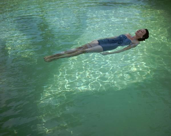 Outdoor Photograph - A Model Floating In A Swimming Pool by John Rawlings