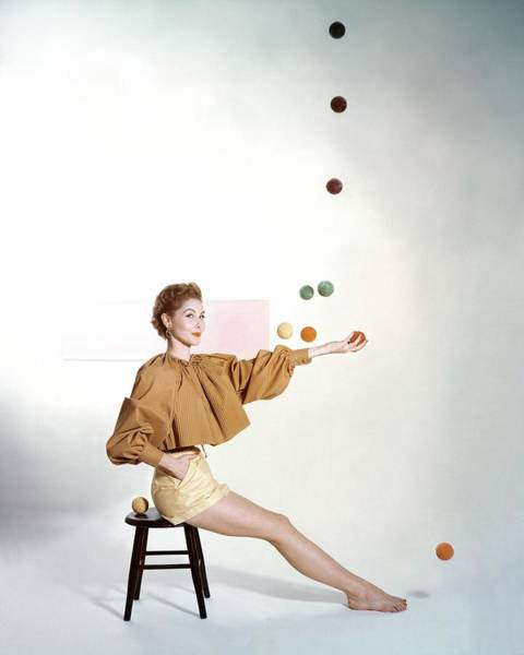 Yellow Background Photograph - A Model Sitting On A Stool Juggling by John Rawlings
