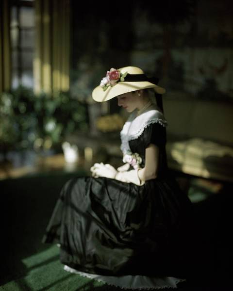 Photograph - A Model Wearing A Black Dress And Sun Hat by John Rawlings