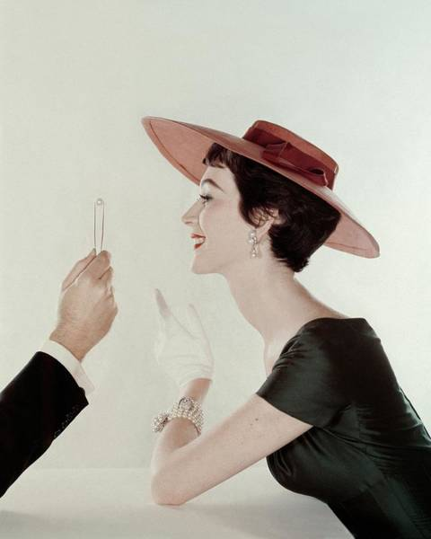 Photograph - A Model Wearing A Sun Hat And Dress by John Rawlings