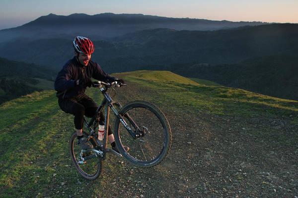 Exuberance Photograph - A Mountain Biker Pops A Sweet Wheelie by Eric Rorer