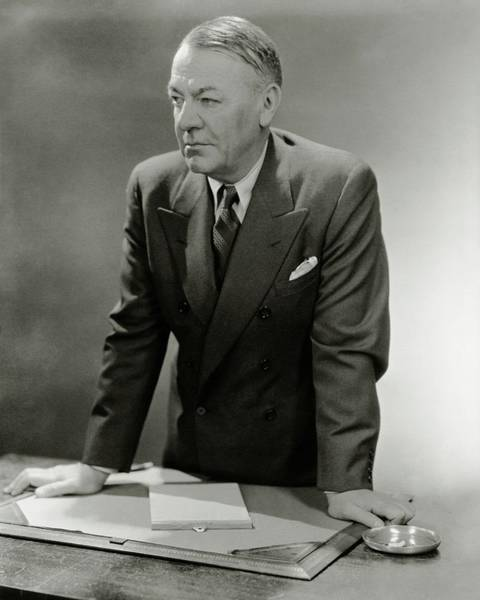 Wine Photograph - A Portrait Of Hugh Johnson Leaning Against A Desk by Lusha Nelson