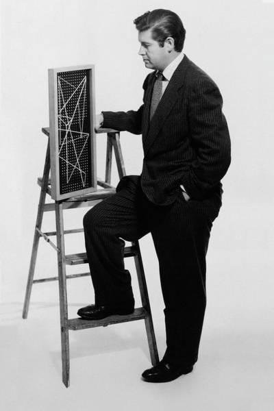Wall Art - Photograph - A Portrait Of Paul Mccobb Leaning On A Ladder by Herbert Matter
