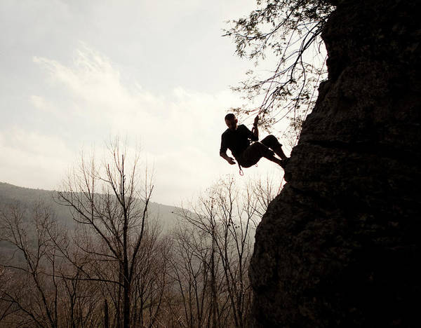 Hanging Rock Photograph - A Rock Climber Is Silhouetted by Chris Bennett