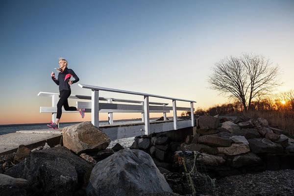 Running Water Wall Art - Photograph - A Runner Crosses A Seaside Bridge by Colin Keaveney