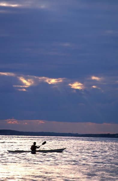 Casco Bay Photograph - A Silhouette Of A Man Sea Kayaking by Corey Rich
