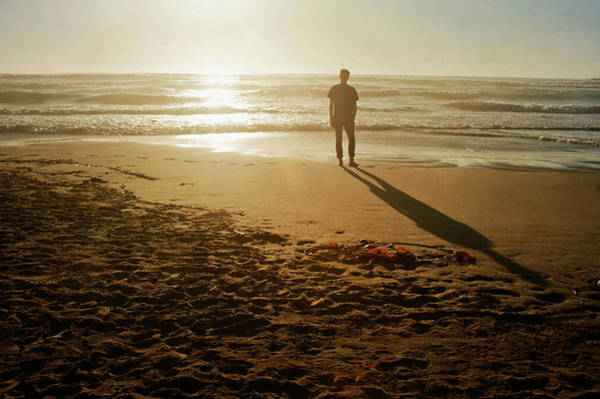 Silhouette Photograph - A Silhouetted Figure Standing On A Beach by Tracy Packer Photography