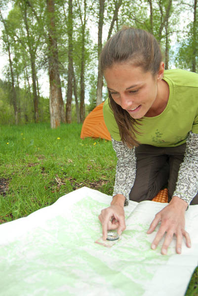 Wall Art - Photograph - A Smiling Young Woman Uses A Map & by Jeff Diener